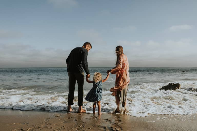 parents with child at beach